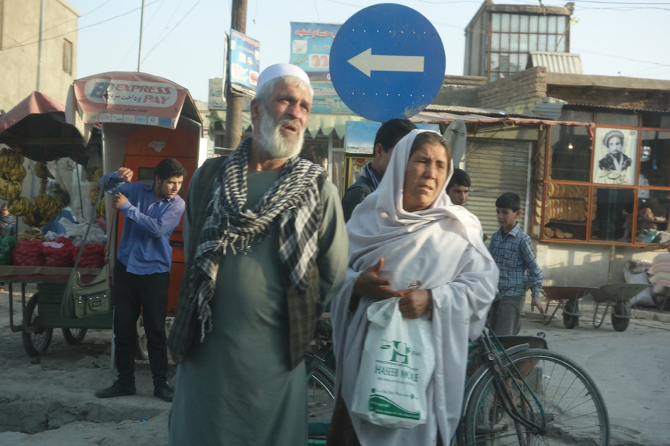 A couple waits to cross Airport Road, early in the morning.